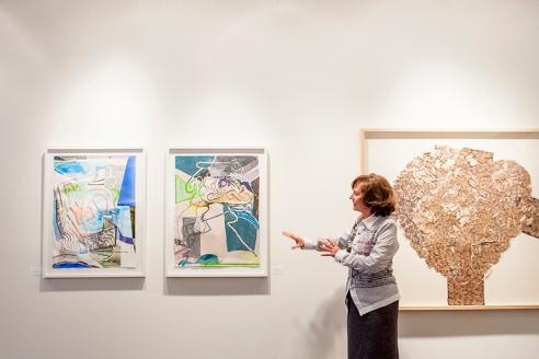 Mme Nicole Brière nous partage son point de vue à propos de deux œuvres de l'artiste canadien, Ryan Sluggett.  À sa droite, une œuvre de Josée Landry Sirois.   Crédit photo:  Isabelle Houde Photographe