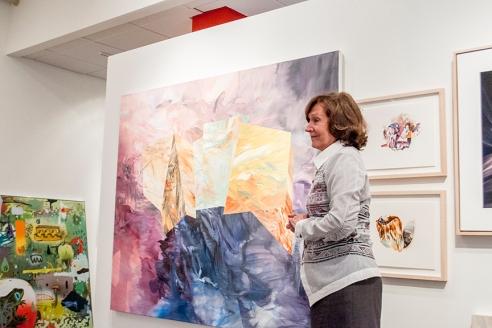 Mme Nicole Brière devant des œuvres de Mélanie Authier.  Sur le mur du fond, à droite, un aperçu d'un tableau de Dan Brault.  Crédit photo:  Isabelle Houde Photographe