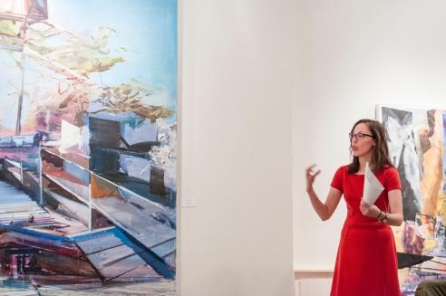Andréanne Lesage - Historienne de l'art avec, à sa droite, un tableau de Martin Golland.  À sa gauche, un aperçu d'une œuvre de Michael Smith.  Crédit photo: Isabelle Houde Photographe